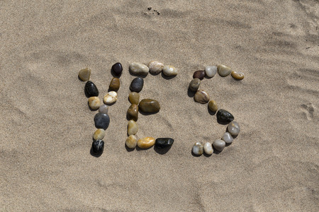 pedagogic: A set of pebbles in a sandy beach forming the word yes Stock Photo