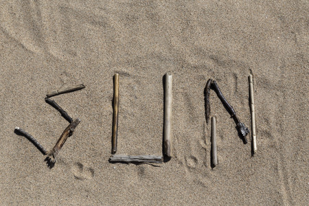 pedagogic: A set of sticks in a sandy beach forming the word sun Stock Photo