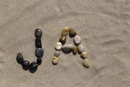 pedagogic: A set of pebbles in a sandy beach forming the swedish word for Yes Stock Photo