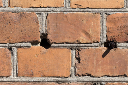 hole in one: A detailed photo of a brick wall with all the damaged parts and the plaster. This one also have a hole and a bolt sticking out Stock Photo