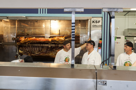 only 3 people: Munich - Germany September 20, 2014: Its not only beer that is served during the Oktober fest, people here are consuming a lot of food and there is a need for persons that fix the food.  This photo is of parts of that staff, 3 males and some meat om the