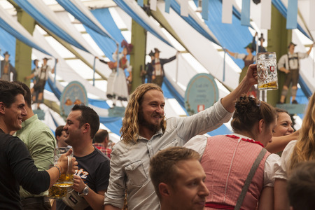 prost: Munich - Germany September 20, 2014: A man in the middle of the picture is having a toast to some of his friends during the Oktober Fest  A man in the middle of the picture is having a toast to some of his friends during the Oktober Fest in one of the ten