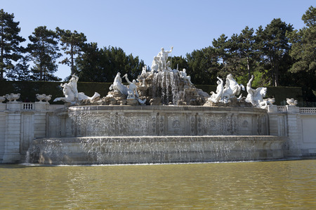nbrunn: A fountain with some statues. Water in the foregrund, trees in the background