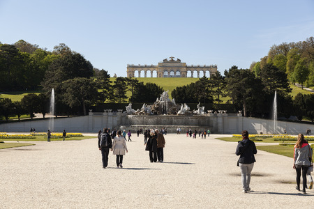 nbrunn: Vienna, Austria - April 18, 2014: Person walking around in the park in Schnbrunn facing the monument on the hill Editorial