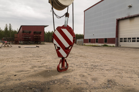 lifting hook: A lifting hook for a industrial crane with some storage buildings in the background