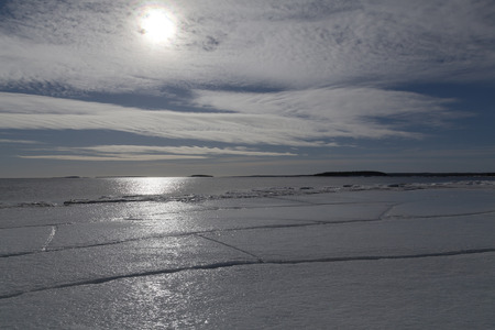 cracks in ice: A piece of ice on an beach with cracks all over and the sund behind the clouds.