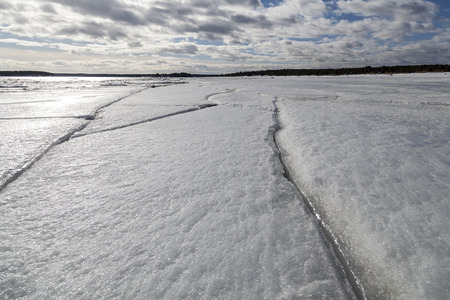 cracks in ice: Ice with long cracks on a beach and clouds and sky in the background