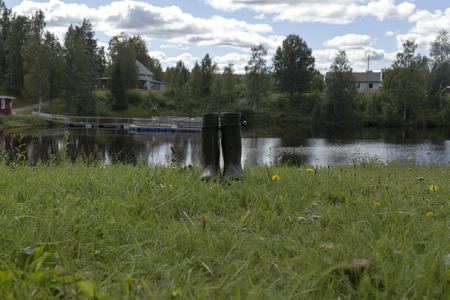sweden resting: A pair of boots in front of a river with buildings in the background