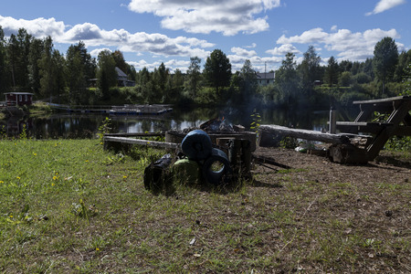 sweden resting: camping and fishing equipment in a park area with a fire Stock Photo