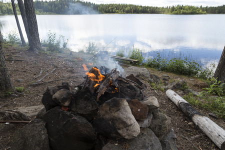 sweden resting: A fire with some smoke in front of a fishing lake Stock Photo