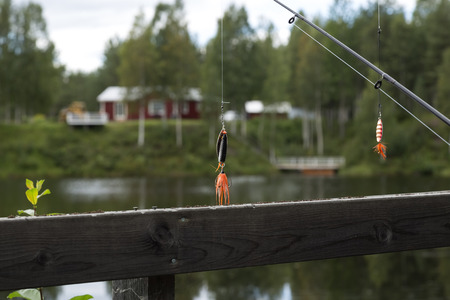 sweden resting: A couple of lures hanging from fishing rods in front of a river Stock Photo