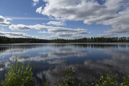 sweden resting: A fishing lake in the wilderness of north sweden with reflections from the sky Stock Photo