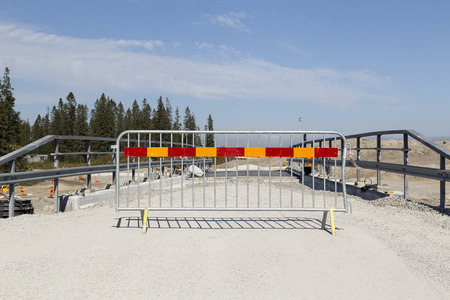 road barrier: A road barrier in front of a bridge on a construction site