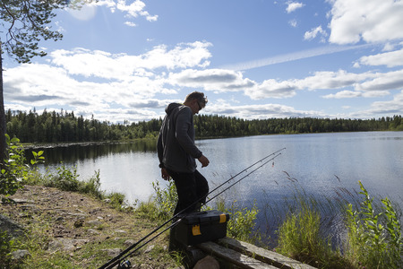 sweden resting: A person standing in front of a lake with two rods and a cloudy sky Stock Photo