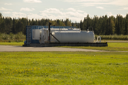 fuel tanks: Fuel tanks on an air field with some grass in the foreground and forest in the background