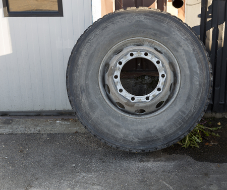 leaned: An isolated tire leaned against a wall Stock Photo