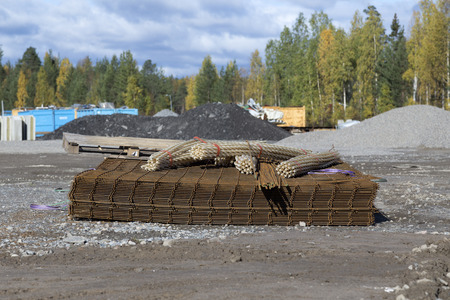 construction material: A pile of construction material on a field with some trees in the background Stock Photo