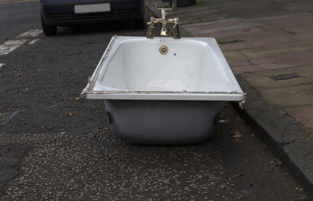 walk board: A bath tub on the street in front of a car