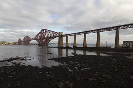 shore line: A bridge for trains over some water with a shore line in the foreground