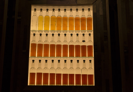 aging process: A line of whiskey bottles to show the aging process