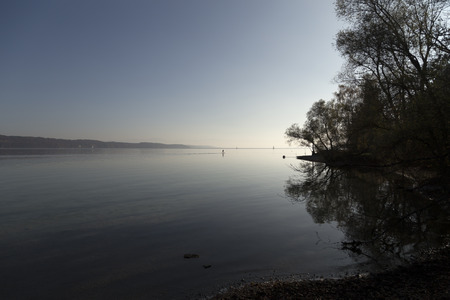 paddler: A lake with some boats and a paddler in the autumn morning