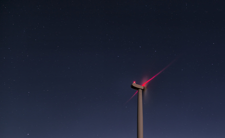 warning system: A wind turbine in the night. Sky full of stars and some red light from the warning system reflecting the wings.