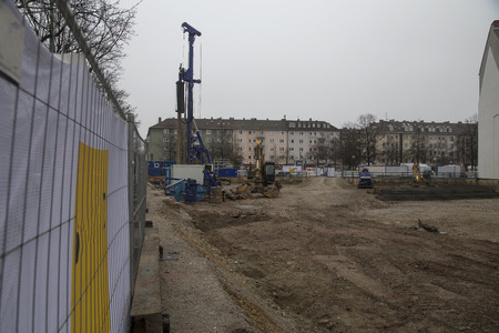 fence: A site for a new building withsome machines and cranes