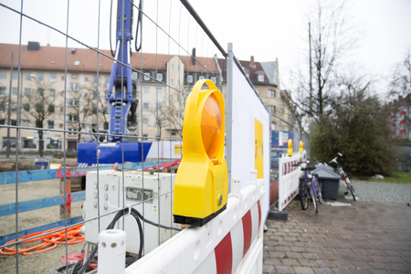 construction site: A warning light in front of a construction site with a crane in the background