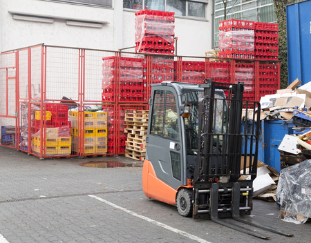 fork lift: A fork lift in front of a building and a garbage container Stock Photo