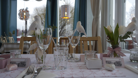 low perspective: A table decoration with straws, glasses and birds from a low perspective with trees in the background Stock Photo