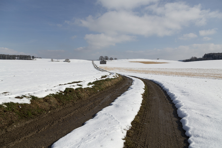 mud snow: A long muddy road through a winter landscape Stock Photo