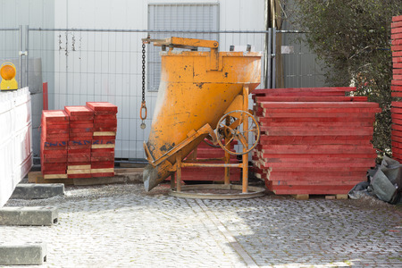 sited: A concrete container on a construction sited with some timber laying in piles