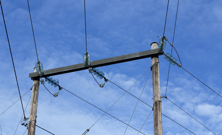 coils: A group of power lines and coils on some wooden poles with clouds in the background
