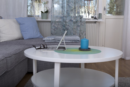 cosily: A tablet and a pair of glasses on a table in a living room Stock Photo
