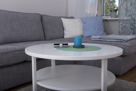 cosily: A phone and a candle in the middle of a table in a living room