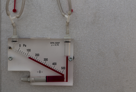wall mounted: A wall mounted measuring unit with a scale and red fluid Stock Photo
