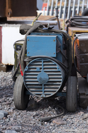 welding machine: An electrical welding machine with a cord on the ground Stock Photo