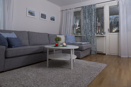 cosily: A sofa and a table with burning candles and a flower Stock Photo