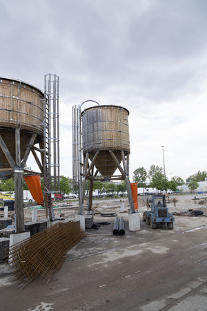 on rebar: A pair of silos on a construction site with some rebar Stock Photo
