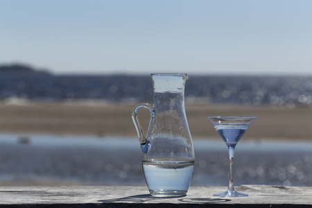 finery: A jug and a glass with water in front of the ocean
