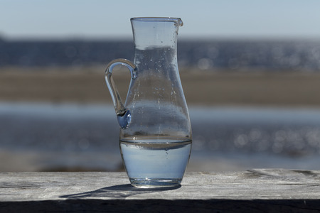 finery: A jug with water in front of the ocean Stock Photo