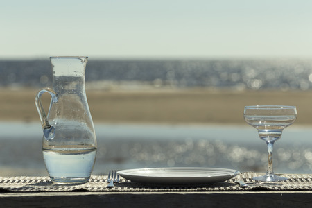 finery: A table with a plate, fork, knife and a glass at the reflecting ocean Stock Photo