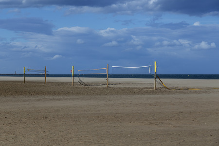 beach volley: A beach volley net on the sandy beach with some clouds in the background