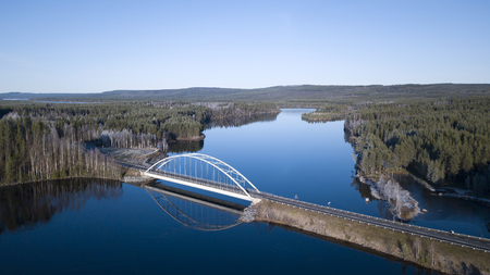 A bridge over a blue river from an aerial perspective