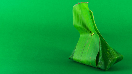 nontoxic: Thailand dessert wrapped in banana leaves lay on a green style.