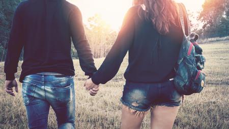 愛好家は、ロマンチックな夕日、ロマンチックな雰囲気に手に手を歩きます。
