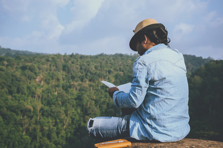 Asian man travel relax in the holiday. seats relax read books on rocky cliffs. On the Moutain. In Thailand Stock Photo