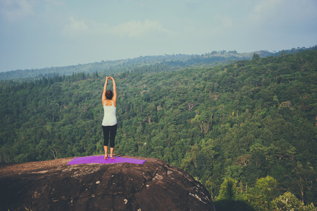 Asian woman doing yoga on mountain cliff