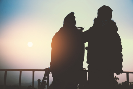 Asian couple looking at sunrise on the mountain Imagens