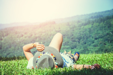 Asian women travel relax in the holiday. Sleep relax on the lawn on the mountain. In Thailand